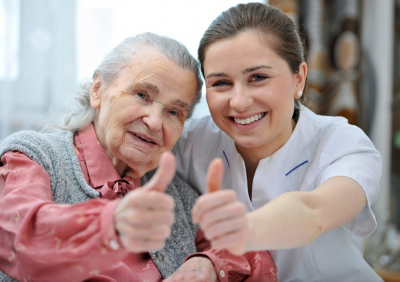 senior woman and caregiver doing thumbs up