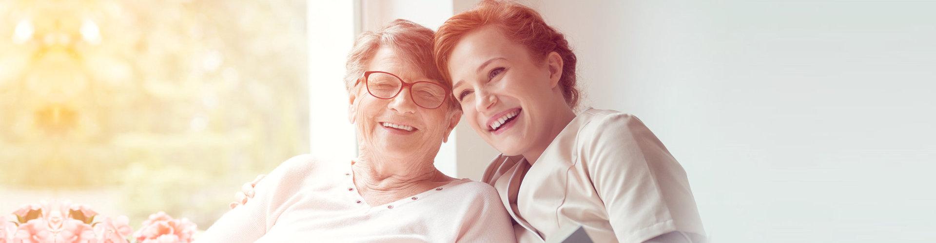 senior woman and caregiver smiling